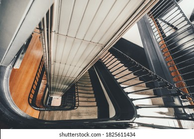 Wide-angle view from above of a long stairwell going down in a spiral in an old dwelling house with a metal railing and a lift shaft in the center, selective focus in the foreground, Lisbon, Portugal