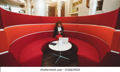 Wide-angle view of an African-American woman entrepreneur sitting inside of the area of a red round sofa in an office with a small white table in the center and a laptop on it and using her smartphone