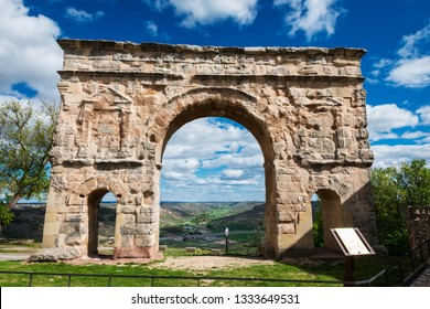 Wide-angle view of the ancient Roman gate in Medinaceli, Spain (1st century AD), against a cloudy blue sky.