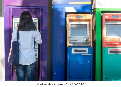 Wide-angle view of a curly businessman in a formal suit using an outdoor cash dispenser to increase his account; man entrepreneur is withdrawing money using a street ATM in urban settings