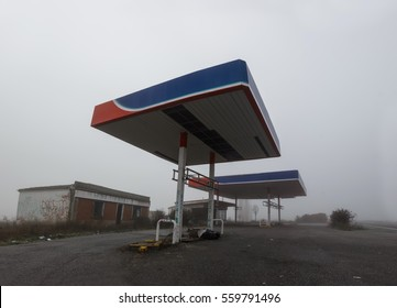83b472de745663 Wide-angle view of derelict gas station next to the road in a winter foggy