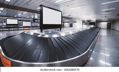 Wide-angle view of an empty luggage conveyor belt with the rubber sections and blank white LCD informational screen mockup on the top and behind; bright arrival zone of a contemporary airport terminal