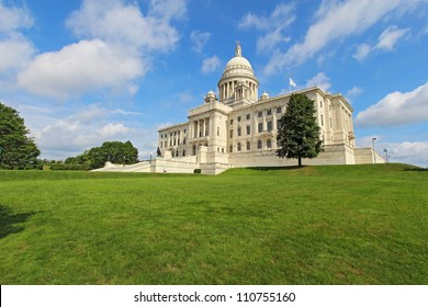 Wide-angle view of the front of the Rhode Island state capitol building as it sits on Capitol Hill in Providence with bright blue sky and white clouds in the background