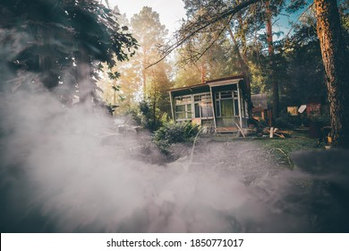 A wide-angle view of an old desolate one-story summer shack with glass veranda surrounded by conifer trees and bushes of the garden and lit by the warm evening sun, with a smoke in the foreground