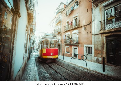 A wide-angle view of a red retro tram on a narrow street with one-way rail traffic in a European city; a vintage tourist streetcar in yellow and red colors on a tramway track over paving stone