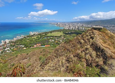 Wide-angle view of the rim of Diamondhead Crater, Waikiki Beach and all of Honolulu in the distance from the top of the trail