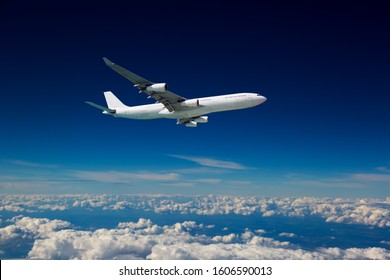 Wide-body passenger plane flies in the blue sky over the clouds. Side view of aircraft.