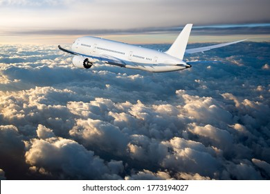 Wide-body passenger plane flies in the blue sky over the clouds. Side view of aircraft. Sunset time.