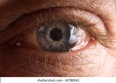 Widely open elderly man's eye closeup