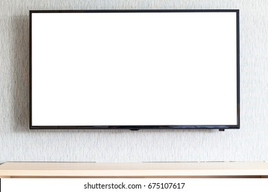 The wide-screen Led tv on the wall background with beautiful nature program and wood shelf for product display.