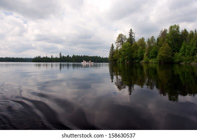 Wideshot of a lake in the Boundary Waters, Minnesota. Sky, clouds, trees and canoe reflected.