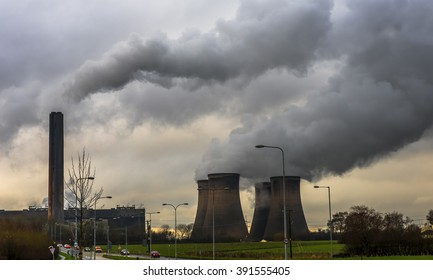 Widnes, Cheshire, Fiddler's Ferry coal powered power station in late evening in winter with clouds of smoke from the chimney and vapour from the cooling towers.