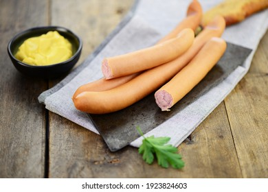 Wiener sausages with mustard on the knife
