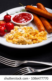Wiener Sausages and scrambled eggs with spices in a dish on black background.