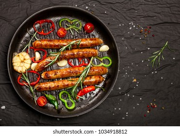 Wiener Sausages with vegetables and spices in a pan on black background