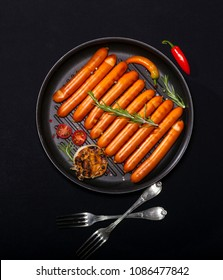 Wiener Sausages with vegetables and spices in a pan on black background with copy space