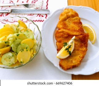 Wiener Schnitzel. Bread crumbed and fried veal scallop with potato and cucumber salad
