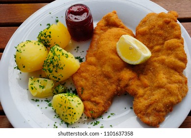 Wiener schnitzel made of pork and served with boiled potatos, cranberry jam and lemon