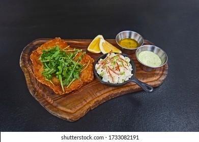 Wiener Schnitzel on wooden board.