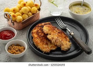 Wiener schnitzel with potato balls and lemon sauce. Breaded Chicken Schnitzel with Garnish.