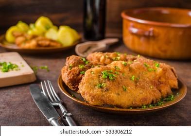 Wiener schnitzel with potatoes and herbs on top