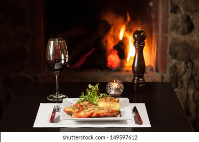 Wiener schnitzel topped with a rich tomato sauce and melted cheese with fire background