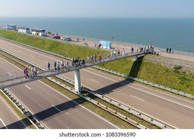 Wieringen, The Netherlands - April 20, 2018: Tourists at catwalk visiting the monument at the location where the afsluitdijk is closed. The dike is the connection between Friesland and Noord-Holland.
