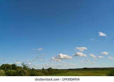 Grüne Wiese und blauer Himmel mit weißen Wolken im Sommer in Mecklenburg-Vorpommern