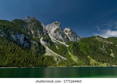 Wiew from lake shore up to well known ferrata in the Austrian Alps Intersport Klettersteig at Gosauseen or Vorderer Gosausee lake, Salzkammergut region, Upper Austria. Dachstein summit and glacier.