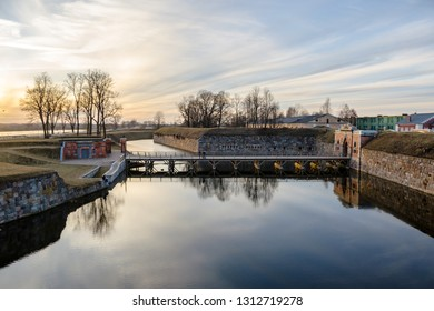 Wiew of restored landscape of Daugavpils Fortress with few people walking on the bridge in the sunset.