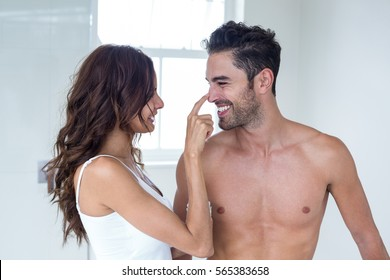 Wife applying cream on shirtless husband face at home