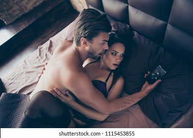 Wife is calling! Oh no unbelievable! Wife arrives comes earlier! Top above overhead view photo of wondered frightened two naked bare lovers under blanket in bed looking at telephone in hand
