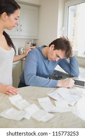 Wife comforting stressed husband over bills in kitchen with tablet pc