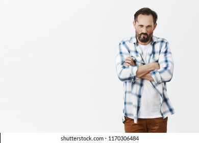 Wife forgot about his birthday, being offended and insulted. Annoyed and angry funny mature caucasian man with beard, frowning and sulking from disappointment, holding hands crossed on chest