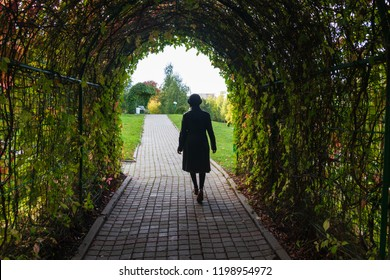 The wife is gone. A woman leaves through a tunnel of wild grape leaves