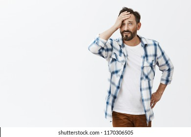 Wife got drunk, husband being embarrassed, cannot look at woman, being humiliated, holding palm on forehead and staring with displeased expression, touching waist, standing over gray background