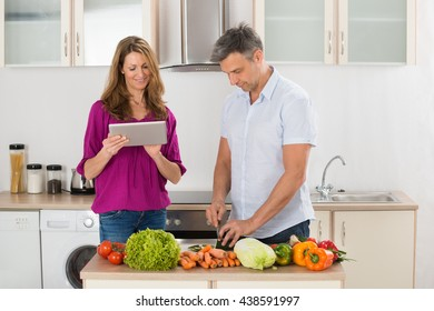 Wife Helping Her Husband For Preparing Food With Digital Tablet