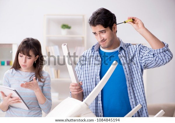 Wife helping husband to repair broken chair at home