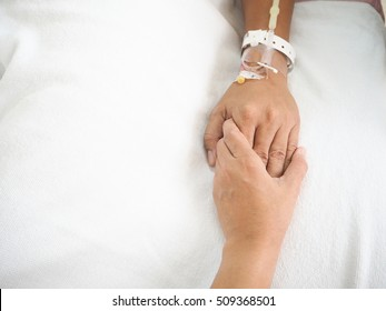 wife holding husband 's hand who fever patients have IV tube