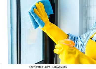 Wife housekeeping and cleaning concept, Happy young woman wiping dust using a spray and a duster while cleaning in glass at home.