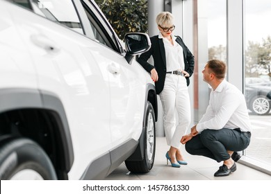 Wife and husband choose a car in dealership. Woman leaned on the car and man sits next it