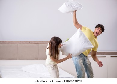 Wife and husband having pillow fight in bedroom