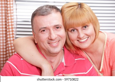 Wife and husband in middle age hugging and smiling