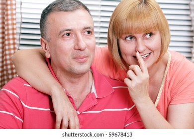 Wife and husband in middle age smiling and looking with interest. Focus on woman.