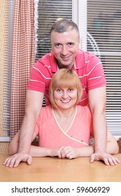 Wife and husband in middle age standing in the kitchen smiling