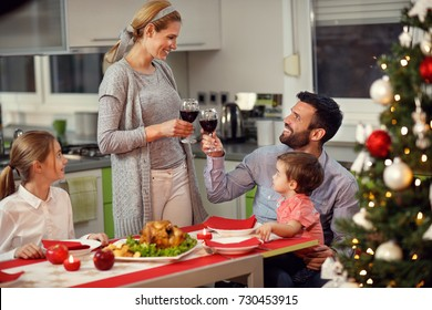 Wife with husband toasting with red wine during gala Christmas dinner