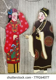 Wife in the red dress and husband in the black suit show in Chinese traditional opera characteristic stucco on the wall.