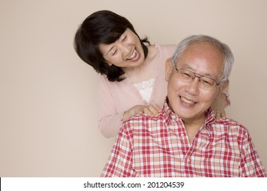 The wife rubbing the shoulder of her husband
