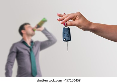 Wife showing car keys and her unfocused husband drinking alcohol on the party