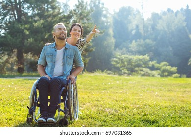 Wife showing something in distance to her disabled husband